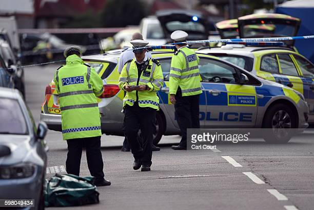 A police officers attend the scene where a woman and a boy were killed when a car being chased by police mounted a pavement and crashed on August 31...