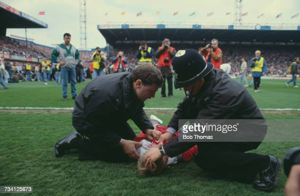 Police officers attend to a casualty on the pitch at Hillsborough football stadium in Sheffield after a human crush at an FA Cup semifinal game...