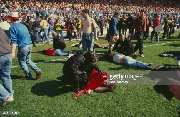 Police officers attend to casualties on the pitch at Hillsborough football stadium in Sheffield after a human crush at an FA Cup semifinal game...