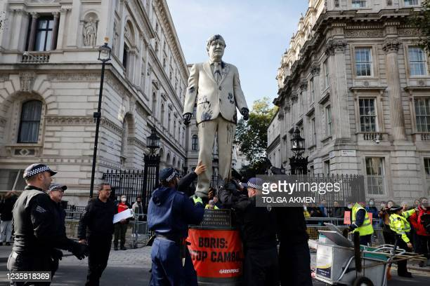 Police officers begin to remove an oil-splattered statue of British Prime Minister Boris Johnson made by artist Hugo Farmer and installed by...