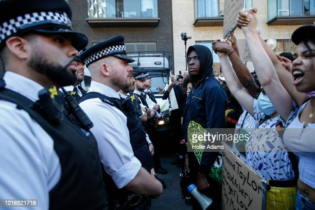 Police officers block a road close to the Embassy of the United States of America as people holding placards join in a spontaneous Black Lives Matter...