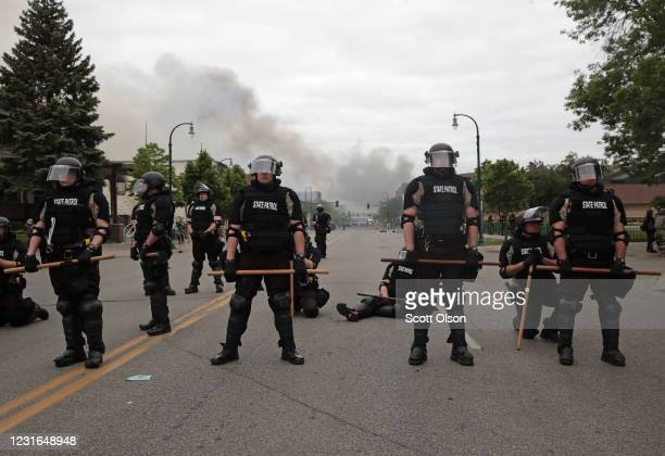 Police officers block a road on the fourth day of protests on May 29, 2020 in Minneapolis, Minnesota. The National Guard has been activated as...