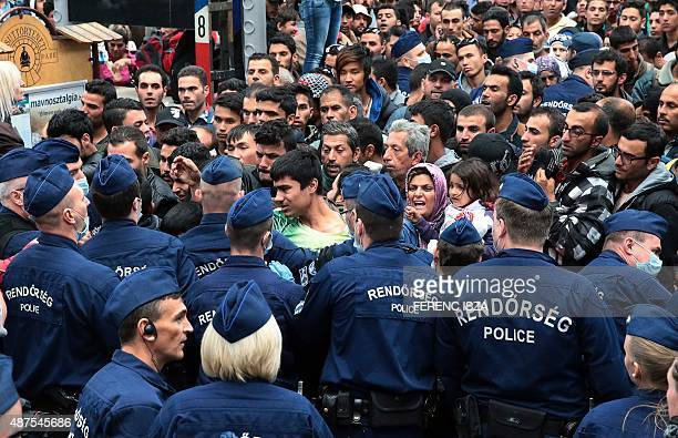 Police officers block migrants in order to prevent them from overcrowding trains at Keleti railway station in Budapest on September 10 2015 Hungary's...