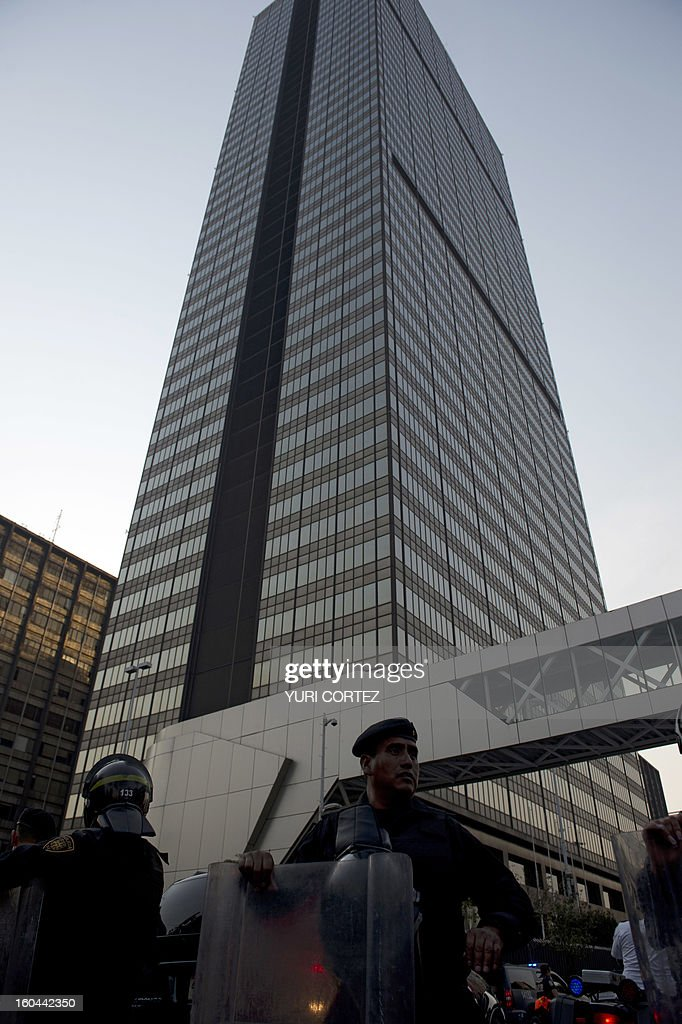 Police officers block off the premises of the skyscraper that houses the headquarters of state-owned Mexican oil giant Pemex in Mexico City on January 31, 2013, following a blast inside the building. An explosion rocked the skyscraper, leaving up to now 14 dead and 40 injured, as a plume of black smoke billowed from the 54-floor tower, according to official sources. AFP PHOTO/Yuri CORTEZ