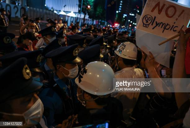 Police officers block protestors protesting against the Tokyo 2020 Olympic Gmaes oustide the Olympic Stadium during the opening ceremony of the Tokyo...