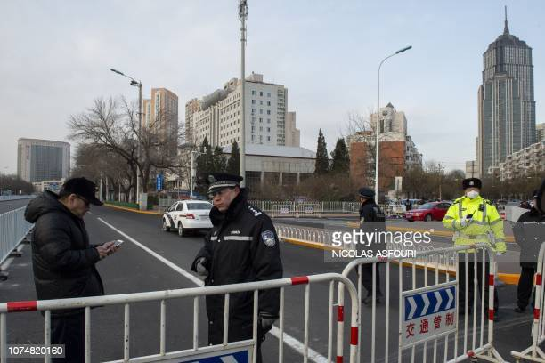 Police officers block streets in front of the number 2 intermediate people's court in Tianjin on December 26 where the trial of human rights lawyer...
