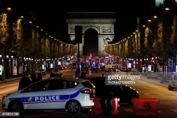 TOPSHOT Police officers block the access to the Champs Elysees in Paris after a shooting on April 20 2017 One police officer was killed and another...