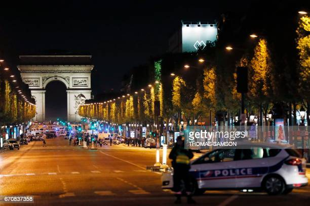 Police officers block the access to the Champs Elysees in Paris after a shooting on April 20 2017 One police officer was killed and another wounded...