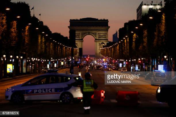 TOPSHOT Police officers block the access to the Champs Elysees near the Arc de Triomphe in Paris after a shooting on April 20 2017 One police officer...