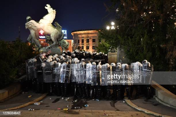 Police officers block the entrance to Serbia's National Assembly building in Belgrade on July 10 after clashes broke out during a demonstration...
