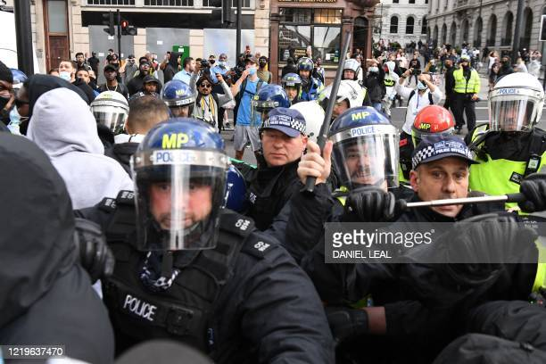 Police officers block the entrance to the Strand after protesters supporting the Black Lives Matter movement clash with opponents in central London...