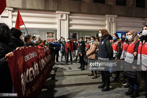 Police officers block the Istiklal avenue, the main shopping street of Istanbul, as they stand in front of women marching during a demonstration...