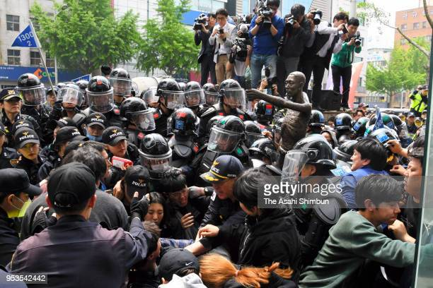 Police officers block the way to the Japanese Consulate General as South Korean labour group attempt to install a statue symbolising Japan's forced...