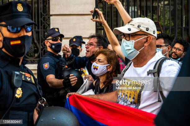 Police officers blocking Colombian protesters during a demonstration against the visit to Madrid Book Fair 2021 of Colombian President Ivan Duque.