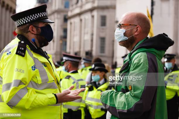 Police officers break up a 'people's assembly' staged by climate change activist movement Extinction Rebellion in Trafalgar Square in London,...