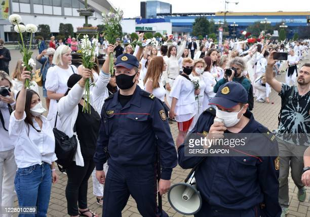 Police officers call demonstrators to go away as women protest against police violence during recent rallies of opposition supporters who accuse...