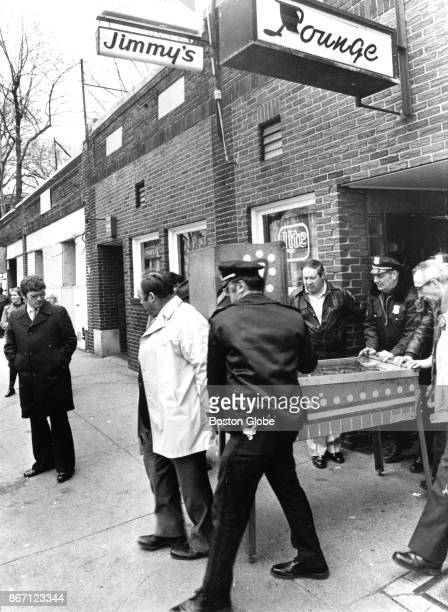 Police officers carry a confiscated illegal electronic pinball gambling machine out of Jimmy's Lounge on Stoughton Street in the Dorchester...