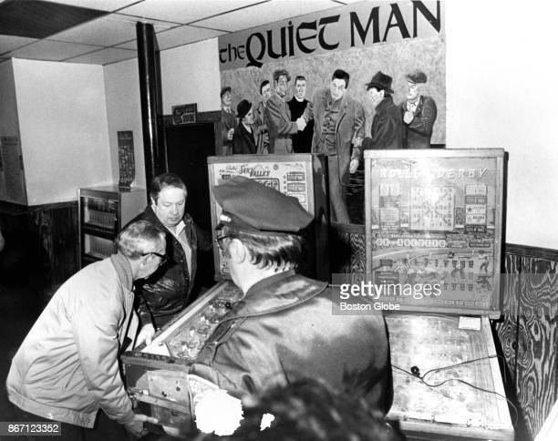 Police officers carry a confiscated illegal electronic pinball gambling machine out of The Quiet Man Tavern in South Boston on Apr 2 1980 State and...
