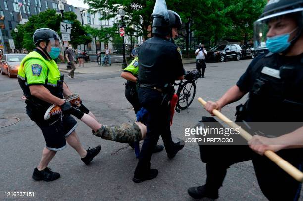 Police officers carry a detained protester after clashes outside the District Four Police station during a Black Lives Matter protest against police...