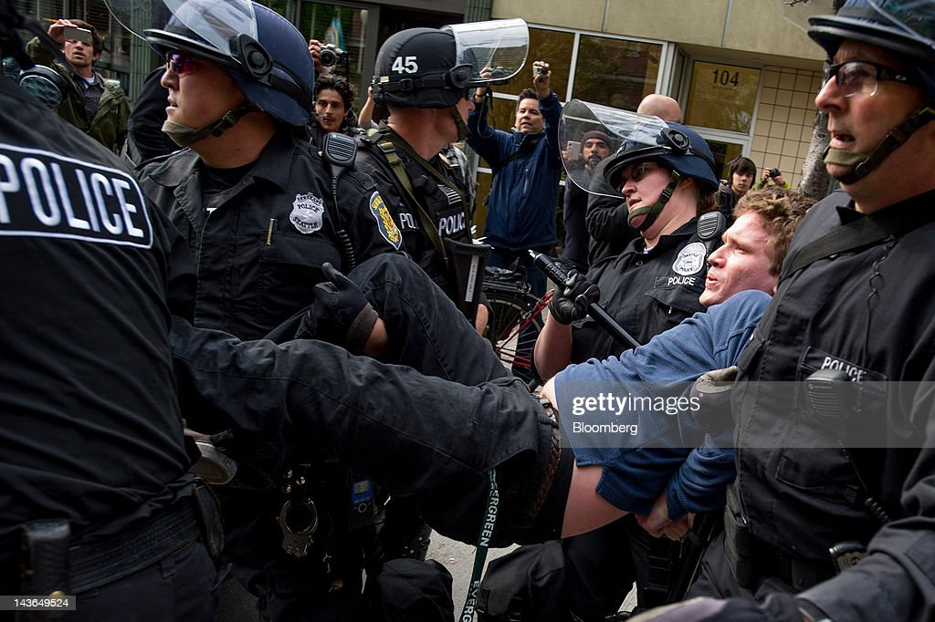 Police officers carry an Occupy Seattle protester, part of an off-shoot of the Occupy Wall Street movement, during a May Day rally and anti-capitalist march in Seattle, Washington, U.S., on Tuesday, May 1, 2012. Occupy Wall Street demonstrators took to the streets in May Day protests from New York to California, picketing banks in Oakland with helicopters overhead and sending a singing 'Guitarmy' to Manhattan's Union Square. Photographer: Stuart Isett/Bloomberg via Getty Images