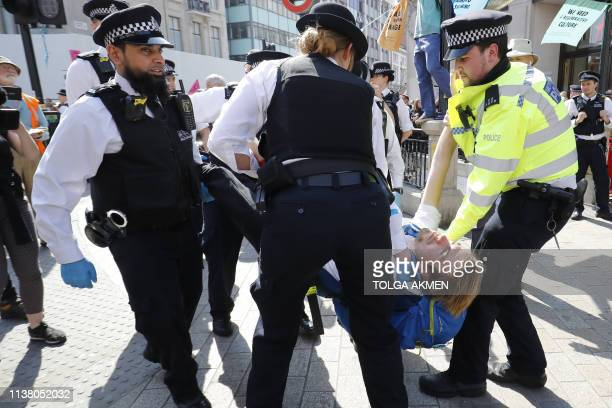 Police officers carry away a climate change activist who was occupying the road junction at Oxford Circus in central London on April 19 the fifth day...