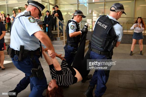 Police officers carry away a refugee advocate following a crackdown on demostrators blocking the main entrance of the Immigration and Department of...