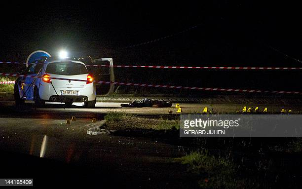 Police officers carry out investigations at the site where a man was found shot dead in a hail of Kalashnikov fire late on May 10 2012 in...