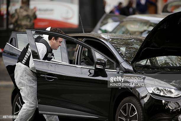Police officers carry out investigations on a car in the 18th district of Paris on November 17 2015 which is suspected to have been involved in the...