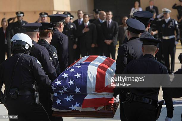 Police officers carry the casket of Los Angeles police Officer Spree Desha who was among the 25 people killed in a train crash towards the Cathedral...