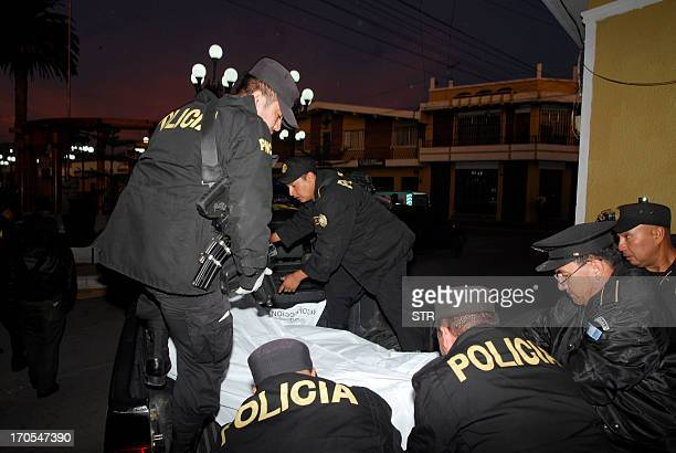 Police officers carry the corpse of one of eight colleagues killed by an armed commando at a police station in Salcaja municipality Quetzaltenango...