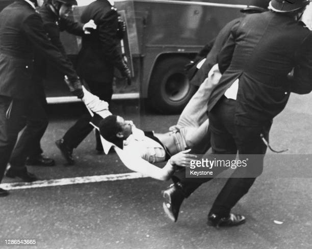 Police officers carrying an arrested man by the arms and legs after violence erupts on the streets of Brixton, London, England, 13th April 1981.