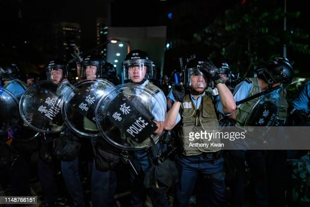 Police officers charge toward protesters after a rally against the extradition law proposal at the Central Government Complex on June 10 2019 in Hong...