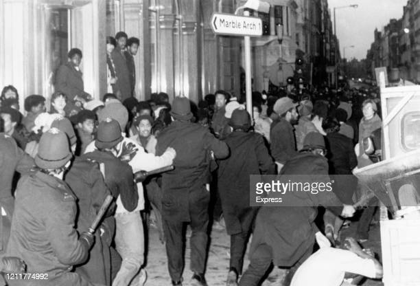 Police officers charging demonstrators during a march to protest against racism and the investigation into a fire in Deptford in which 13 black...