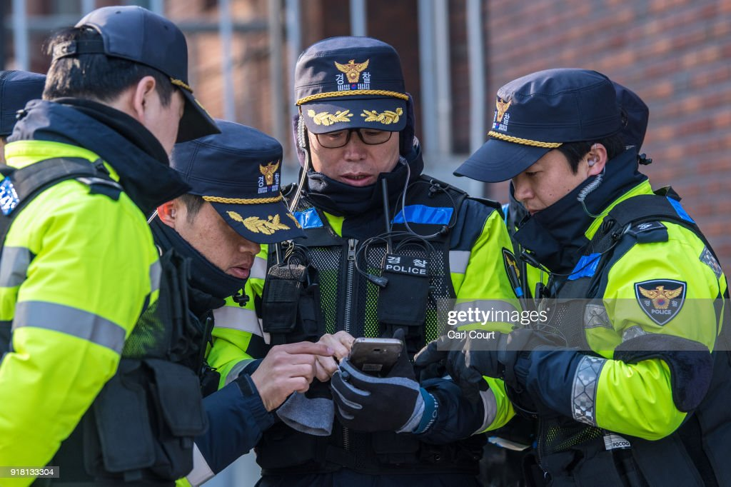 Police officers check a phone as they patrol outside the stadium ahead of the Women's Ice Hockey Preliminary Round Group B game between Korea and Japan on day five of the PyeongChang 2018 Winter Olympics at Kwandong Hockey Centre on February 14, 2018 in Gangneung, South Korea. Strong winds have caused a number of events to be rescheduled at the PyeongChang Winter Olympics including the biathlon and Alpine skiing competitions.