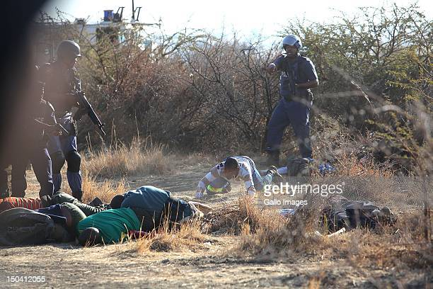 Police officers check bodies lying on open ground after opening fire on striking mine workers outside the Nkageng informal settlement on August 16...