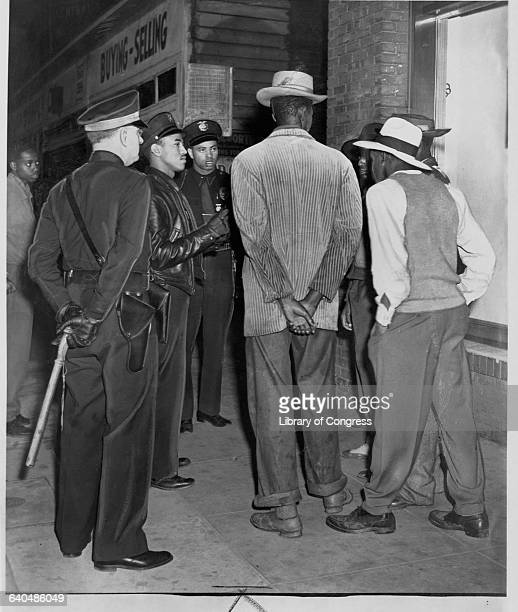 Police officers check draft cards of African American men dressed in zoot suits on the sidewalk of Central Avenue Police officers patrol the area to...