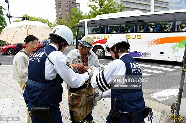 Police officers check inside the bag of a passersby in prepration of the visit by US President Barack Obama on May 27 2016 in Hiroshima Japan Obama...