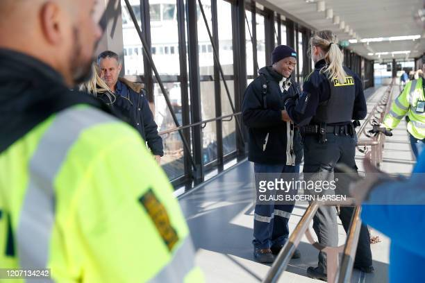 Police officers check passengers disembarking a ferry from Sweden in Elsingoere Denmark before the borders close on March 14 2020 The head of the...