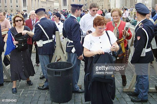 Police officers check the bags of tourists, at St. Peter's Basilica in Vatican City, to guard against terrorism after the terrorist attacks on the...