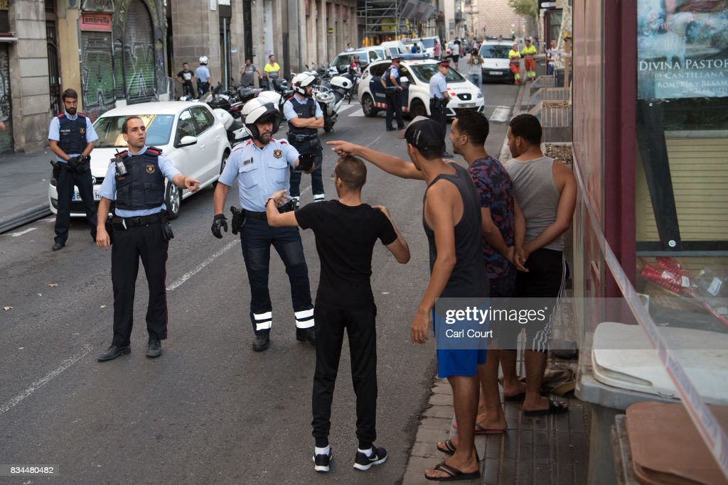 Police officers check the identity of a group of men on Las Ramblas following yesterday's terrorist attack, on August 18, 2017 in Barcelona, Spain. Thirteen people were killed and dozens injured when a van hit crowds in the Las Ramblas area of Barcelona on Thursday. Spanish police have also killed five suspected terrorists in the town of Cambrils to stop a second terrorist attack.