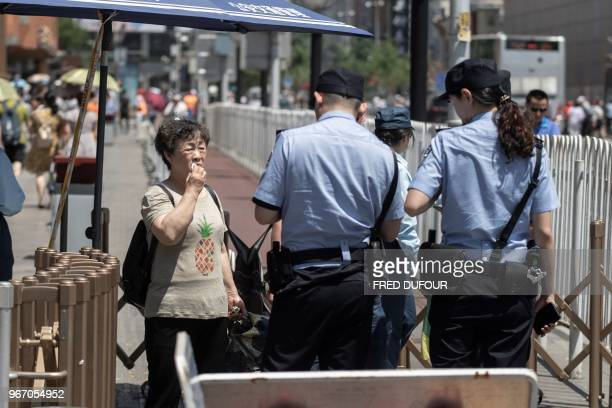 Police officers check the identity of people at a check point near Tiananmen Square on the anniversary of the 1989 crackdown on democracy protestors...