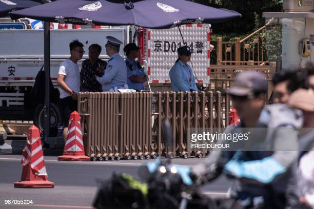 Police officers check the identity of people near Tiananmen Square on the anniversary of the 1989 crackdown on democracy protestors in Beijing on...