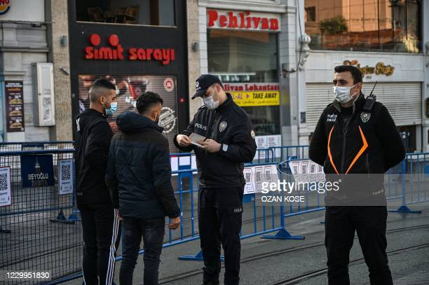 Police officers checks identity papers of people in Istiklal avenue in Istanbul during a week-end curfew aimed at curbing the spread of the Covid-19...