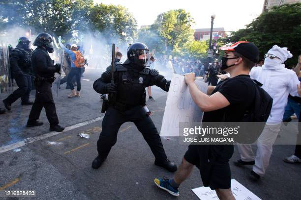 TOPSHOT Police officers clash with protestors near the White House on June 1 2020 as demonstrations against George Floyd's death continue Police...