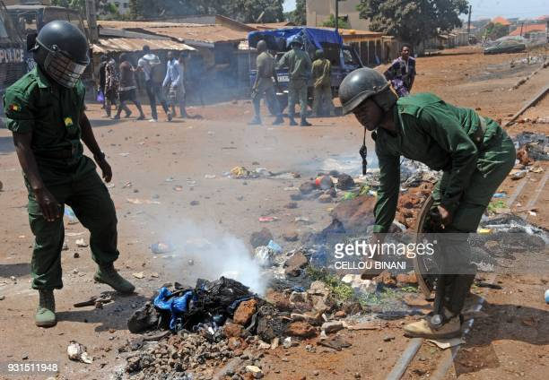 Police officers clear a burning barricade on a street in Conakry on March 13 which was erected by demonstrators during a protest against Guinea's...