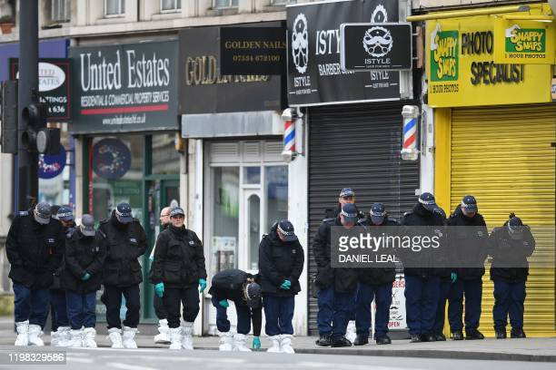 Police officers conduct a search on Streatham High Road in south London on February 3 after a man was shot dead by police on February 2, following...