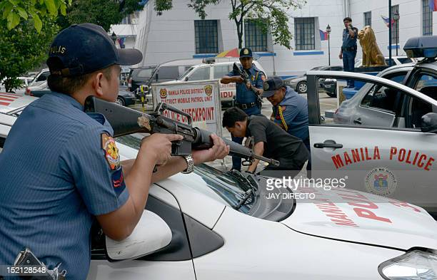 Police officers conduct an exercise on how to apprehend and handle suspected criminals from terrorists to car nappers at the Manila police...
