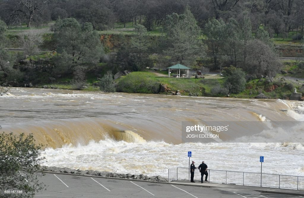 Police officers confer as the Oroville Dam releases water