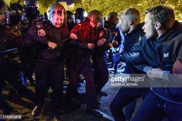 Police officers confront activists protesting against a plan to build an Orthodox cathedral at a construction site in a park in the Russian Urals...