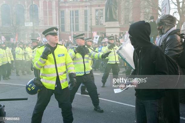 Police officers confront protesters in Parliament Square, London during the organised demonstration against the rise in University Fees